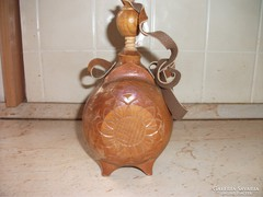 I am selling a bottle decorated with a wooden wood carving.