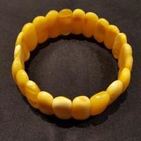 Borostyánkő karkötő sárga opak ovális lapos kövekből gumidamilra fűzve.