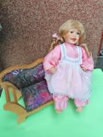 Régi porcelán baba nagy fa kárpitos kanapén